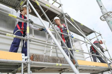 עובדים על פיגומים בשיפוץ בניין